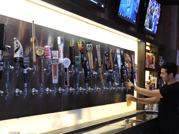 Bartender Cameron Alarco pours a beer from one of the many taps.