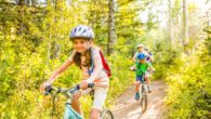 girl riding bike through forest