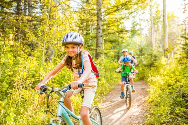 girl riding bike through forest